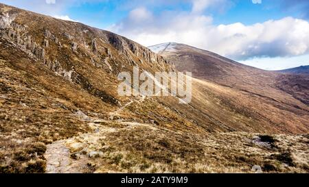 Footpath leading to snow capped peak of Slieve Donard mountain. Mourn Wall surrounding Mourn Mountains, highest range in Northern Ireland - Stock Photo