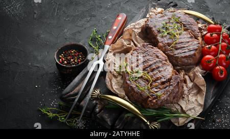 Grilled ribeye beef steak, herbs and spices on a dark table. Top view. Free space for your text. - Stock Photo