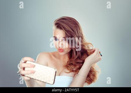 I am beautiful and I know it. Portrait of a young attractive blonde woman making selfie photo on smartphone isolated on a gray background - Stock Photo