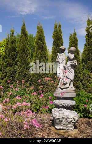 Concrete statue of a young boy and girl, Azalea - Rhododendron 'Northern Lights' bordered by a row of Thuja occidentalis 'Smaragd' - Cedar trees. - Stock Photo