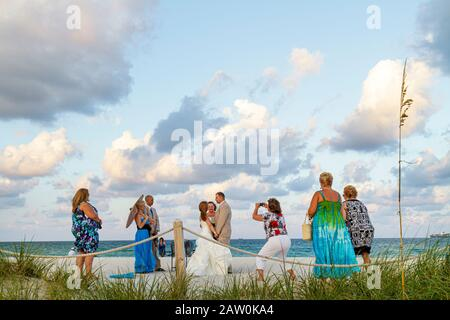 Miami Beach Florida South Pointe Park wedding ceremony public beach vows bride bridegroom guests outside clouds - Stock Photo