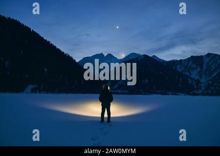 Silhouette of man is illuminating frozen lake with headlamp in the mountains under night sky with stars and moon.
