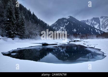 Beautiful landscape of winter mountains reflected at Issyk Lake in Kazakhstan. - Stock Photo