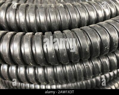 black coiled corrugated insulation tube at warehouse. - Stock Photo