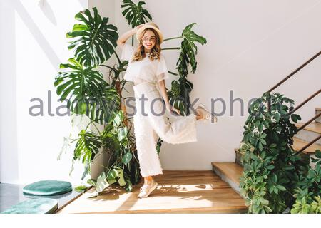Ecstatic blonde girl in white pants funny dancing at home posing in front of big plant. Indoor portrait of jumping young woman in hat and glasses happy smiling next to stairs. - Stock Photo