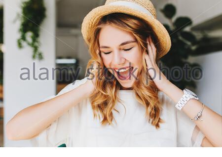 Close-up portrait of ecstatic curly girl wears trendy bracelet and wristwatch laughing with eyes closed. Attractive blonde young woman in summer hat happy posing with mouth open touching her hair. - Stock Photo
