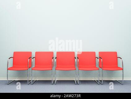 A row of five waiting room chairs in an empty room