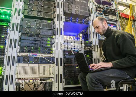 A man with a laptop sits in the server room of the data center. The system administrator works near the racks with the servers. Computer Engineer - Stock Photo