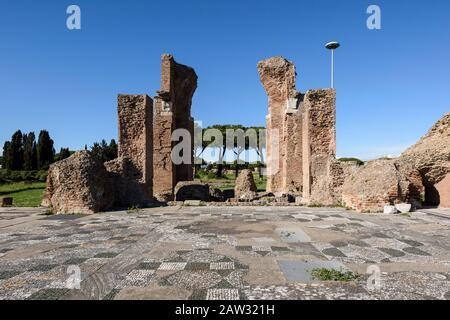 Rome. Italy. Ostia Antica. Terme di Porta Marina (Baths of the Porta Marina). Brick piers of the apse, polychrome geometric mosaic of the frigidarium - Stock Photo
