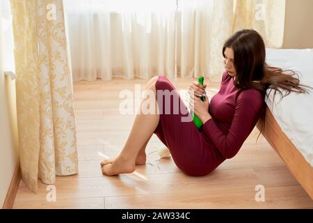 From above view of sad depressed girl in dress sitting of floor and leaning on bed in room. Side view of woman having hangover and holding bottle of alcohol drink. Concept of addiction, alcoholism. - Stock Photo