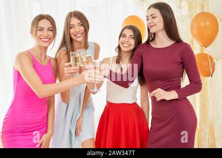 Front view of four young happy female friends celebrating, clinkinkg glasses with champagne in bedroom. Group of girls smiling and looking at camera. Festive mood, balloons around. - Stock Photo
