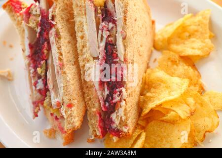 Sandwich made from Thanksgiving leftover turkey, cranberry sauce and stuffing with stuffing-flavored potato chips - Stock Photo