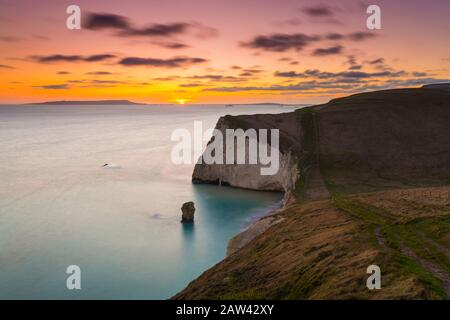Lulworth, Dorset, UK.  6th February 2020. UK Weather.  A golden sunset at Bats Head near Lulworth in Dorset looking west towards Weymouth and the Isle of Portland viewed from the South West Coast Path on Swyre Head.  Picture Credit: Graham Hunt/Alamy Live News