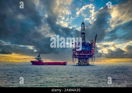 An ocean oil rig and supply ship in the South China Sea near Japan. - Stock Photo