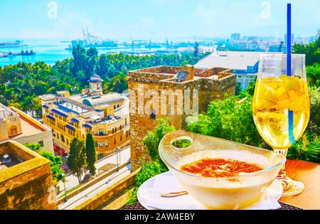 The tasty Spanish rice pudding (arroz con leche) and a glass of sparkling cava sangria in outdoor restaurant with top view on city and port of Malaga, - Stock Photo
