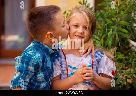 Brother boy are kissing his sister girl on the cheek, warm hugs in nature outside near the house, she smiles happy. Brother and Sister Elementary Chil - Stock Photo