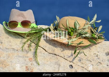 Summer vacation concept, two hats, sunglasses, olive wreath and sprig of rosemary on marble rock against blue bokeh background - Stock Photo
