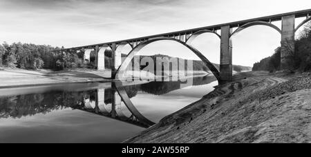 High arched road viaduct above Orlik reservoir. Panoramic black and white view. Podolsko Bridge, Czechia. Muddy bank and mirroring in water surface. - Stock Photo