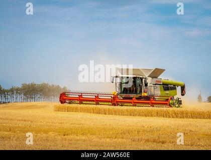 Canterbury, New Zealand - February 2 2020: A large combine harvester working in a barley field in summertime - Stock Photo
