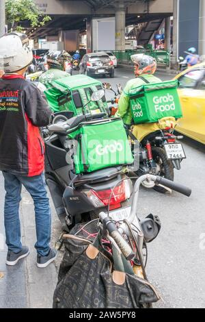 Bangkok, Thailand - January 9th 2020: Grab food motorcyclists on Sukhumvit road. The service is becoming popular in the city. - Stock Photo