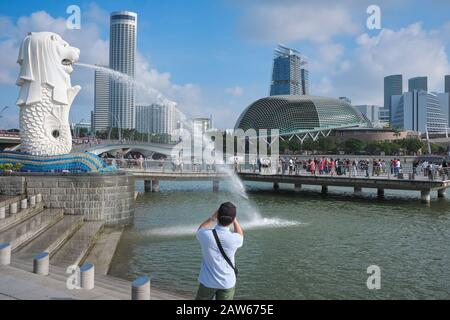 A tourist photographs the iconic Merlion at Merlion Park, Marina Bay, Singapore; b/g: the tower of Stamford Swissôtel (l), Theatres on the Bay (m) - Stock Photo