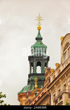 St. Nicholas Church, Gothic gold filigree cross on ornate verdigris cupola & Czech art nouveau architectural facades on Pařížská Street Prague,