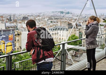 Travellers photograph Paris from the rooftop level of the Centre Pompidou views to Montmartre, and Sacré-Cœur on an overcast day - Stock Photo