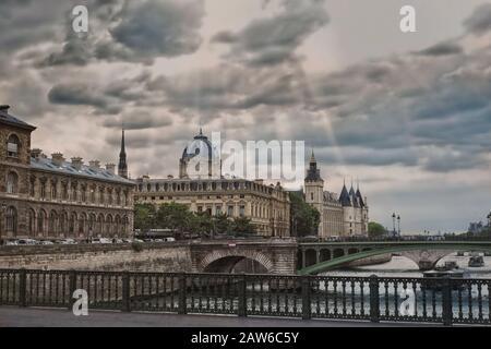 View from Pont d'Arcole of palais de la Cité, Palace of Justice, Palais de Justice and Conciergerie in dramatic light breaking through clouds - Stock Photo