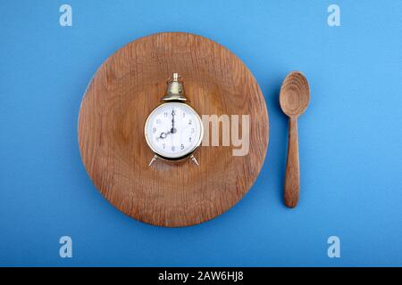 Eight hour feeding window concept or breakfast time with clock on plate and wooden spoon. Overhead view