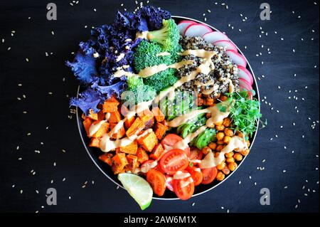 Vegan Buddha bowl with quinoa, baked sweet potato, red kale leaves, spicy chickpea, avocado and micro greens. Healthy balanced eating. Top view - Stock Photo