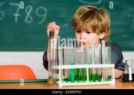 experimenting with chemicals kid in lab coat learning chemistry chemistry lab. Back to school. Little boy at chemical cabinet. Little kid learning chemistry in school laboratory. Scientists at work. - Stock Photo