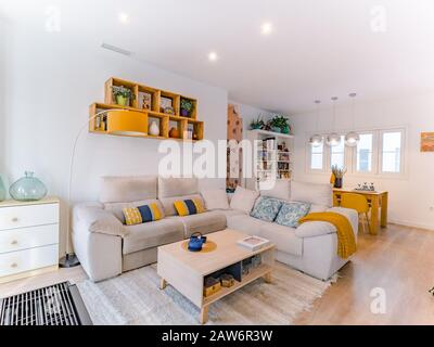 Malaga, Spain. Circa October 2019. Cozy stylish bright living room with natural style, sofa, wooden table, pictures,books and plants. Spacious modern - Stock Photo