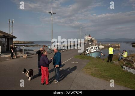 Islanders waiting for the arrival of the Caledonian MacBrayne ferry at Scalasaig from Oban on the the Inner Hebridean island of Colonsay on Scotland's west coast.  The island is in the council area of Argyll and Bute and has an area of 4,074 hectares (15.7 sq mi). Aligned on a south-west to north-east axis, it measures 8 miles (13 km) in length and reaches 3 miles (4.8 km) at its widest point, in 2019 it had a permanent population of 136 adults and children. - Stock Photo