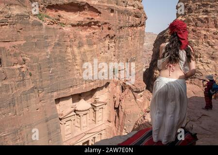 PETRA, JORDAN - MAY 18, 2018: Traveler woman looking down to the archeological site of the Treasury, Petra, part of Unesco Heritage - Stock Photo