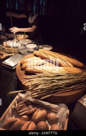 freshly homemade baked traditional bread on wooden table with woman baking bakery at background - Stock Photo