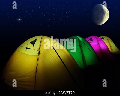 colorful tent glows under a night sky with moon and full of stars. outdoor lifestyle camping with group of friends - Stock Photo