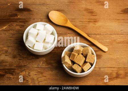 White and brown sugar cubes in white ceramic bowls on a wooden table - Stock Photo