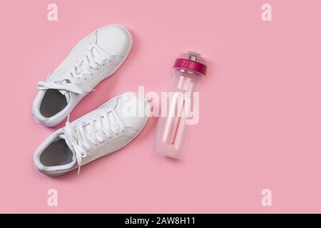 A pair of white sneakers and a sports water bottle on a pink background - Stock Photo