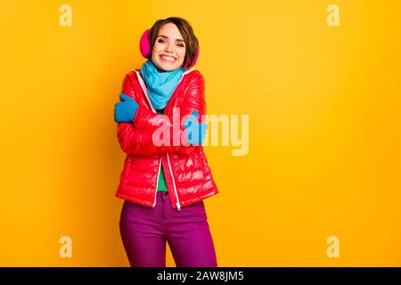 Photo of funny cheerful lady enjoy warm coat in frosty weather hug herself wear casual short red overcoat blue scarf gloves earmuffs pants isolated - Stock Photo