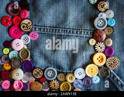 sewing buttons on denim jeans background - Stock Photo