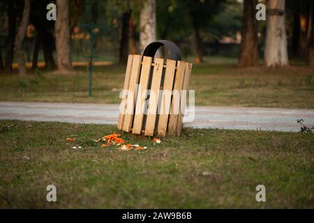 Wooden recycle bin on the sidewalk in the park - Stock Photo