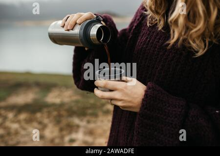 Happy beautiful woman with hat drinking coffee in nature, on a foggy morning Lake and mountains are in the background. She is smiling and poring coffe - Stock Photo