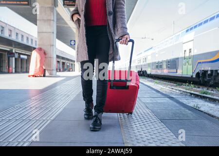 Close up of a woman walking and dragging luggage suitcase bag