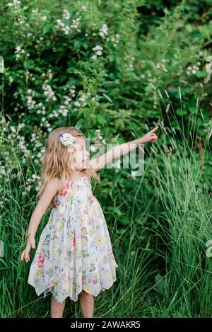 A little girl standing in a meadow and pointing. - Stock Photo