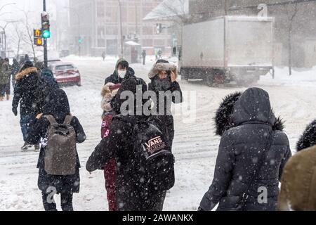 Montreal, CA - 7 February 2020: Pedestrians walking in Downtown Montreal during snow storm. - Stock Photo