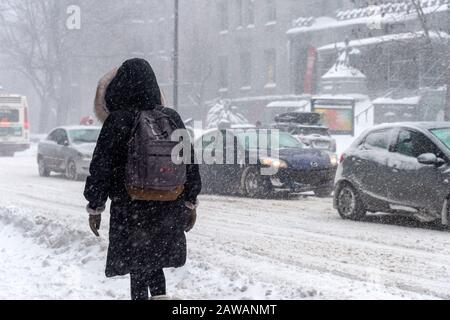 Montreal, CA - 7 February 2020: Woman walking in Downtown Montreal during snow storm. - Stock Photo