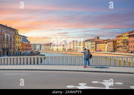 A young couple stops on a bridge over the River Arno to take a photo selfie in the Tuscan city of Pisa Italy on a warm summer day. - Stock Photo