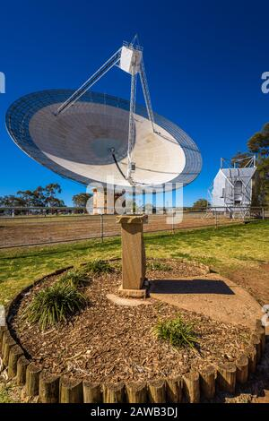 Circular garden with a static compass marker pillar and model satellite lead the eye to the famous Parkes Radio Telescope, in Australia. - Stock Photo