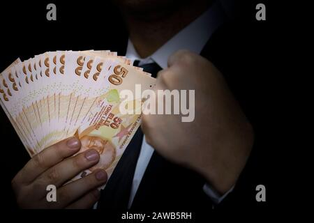 Succesful businessman holding 50 Turkish Lira banknotes in his hand - Stock Photo