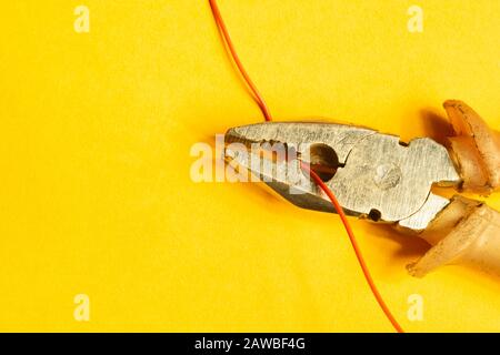 Pliers cuts a red wire on yellow background. work tool. copy space - Stock Photo
